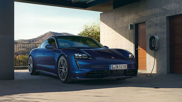 Porsche Taycan in blau an einer Wallbox
