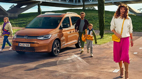 Volkswagen Caddy Life in Orange mit Familie